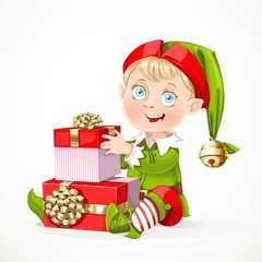 Cute little Santa`s elf sit and puts boxes with gifts  isolated