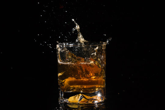 Quality glass of whiskey with splashes from falling slice of lemon on black background.