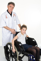 Little girl sitting on the wheelchair supported by a male doctor at the hospital