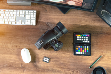 Desktop shot of a modern Digital Photo Camera with Keyboard, Mouse and color checker