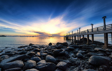 Sea pier sunrise photography with stones and dramatic sky