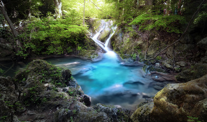 Majestic nature background of mountain river stream and small blue water lake in wild tropical forest