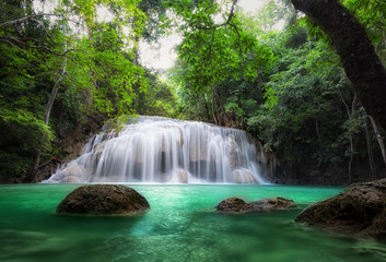 Waterfall in tropical forest. Jungle trees and blue water of mountain river in national park in Thailand