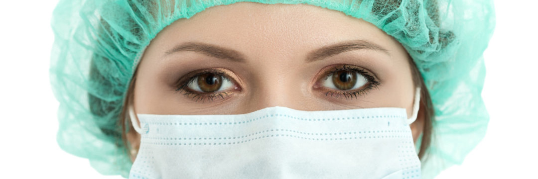 Young woman doctor in cap and face mask close-up portrait
