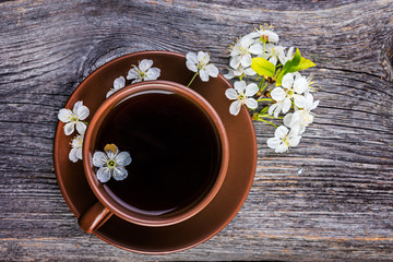 Cup of tea and  cherry  branch on a wooden background.