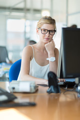 Blonde business assistant at her glass desk looking at camera