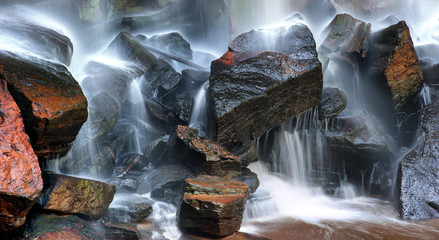 Wet rocks and water streams of mountain river