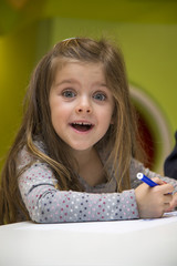 Little girl drawing in the playroom