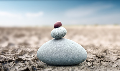 Spiritual and peaceful rock pebble tower on dry deserted land. Zen like conceptual background