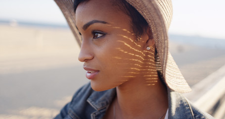 Close up shot of pretty black woman at the beach wearing sunhat