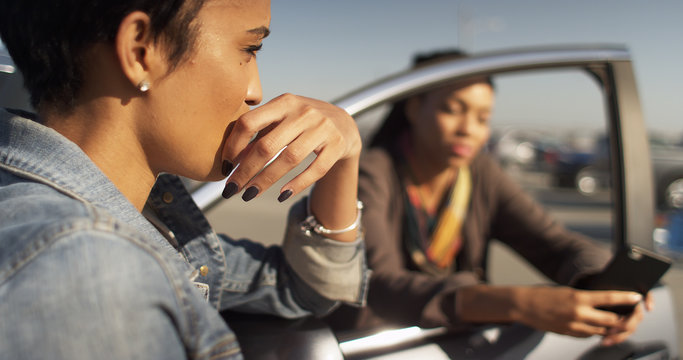 Two black women friends leaning against car talking and texting
