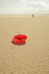 çölde yalnız başına bir insan yerde kırmızı bir şemsiye gündüz manzarası ve güneşli bir havada manzara fotoğraf çekimi Retro tasarım  klip ve sanatçı