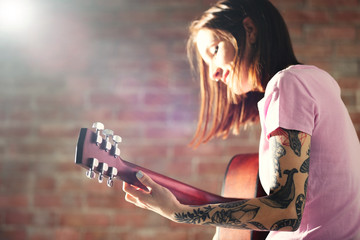 Attractive woman with tattoo playing guitar on brick background