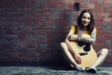 Woman with tattoo and guitar sitting on background on brick background