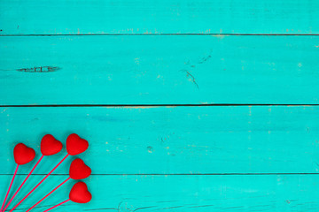 Red hearts on rustic teal blue wood background