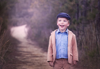 happy little boy wearing a hat standing on a path and smiling