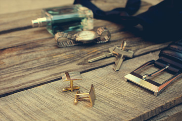 Men accessories: wrist watch, cufflinks, strap, keys, tie, perfume on the old wood background. Toned image.