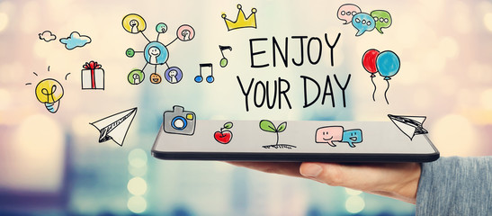 Enjoy Your Day concept with man holding a tablet