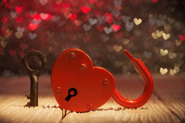 Unlocked heartshaped padlock over abstract Valentines day backgr