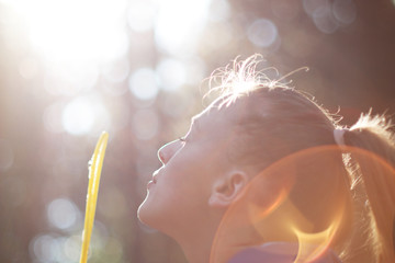 Young woman playfully blowing soap bubbles
