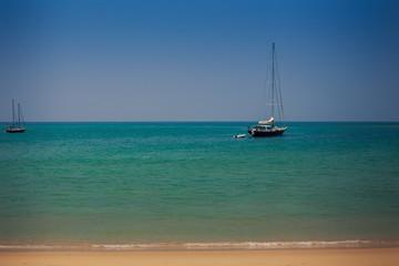 closeup yachts in azure sea near beach against blue sky