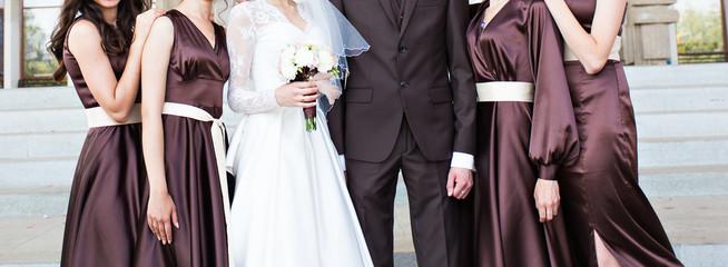Handsome groom in suit hugging elegant bride with bridesmaids