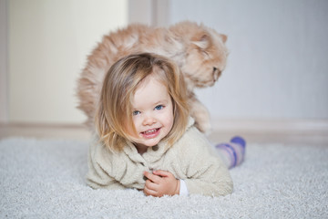 Little girl are playing with a cat
