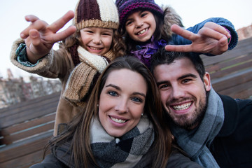 Happy young family taking a selfie in the street.