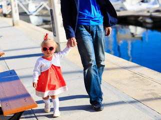 father and little daughter walking in the port