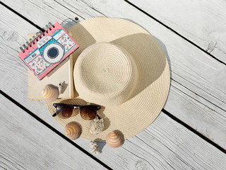 Summer sea vacation. Travel and vacation items on white wooden table. Beach accessories