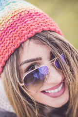 Hipster girl with sunglasses and winter knitted woolen hat