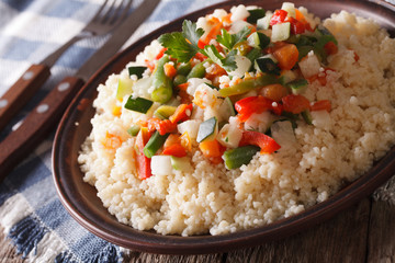 Asian Couscous with vegetables close-up on a plate. horizontal