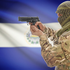 Male with gun in hands and national flag on background - El Salvador