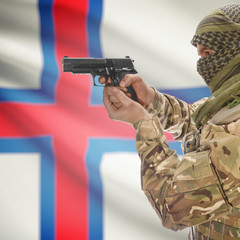 Male with gun in hands and national flag on background - Faroe Islands
