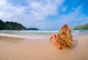 Beautiful young woman portrait laying on the tropical  beach.