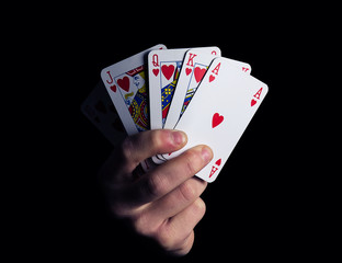 man hand shows royal flush playing card combination close-up on a black background