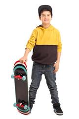 Cute little skater boy holding a skateboard
