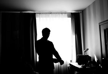 Wearing his favorite shirt. Silhouette of man buttoning   shirt