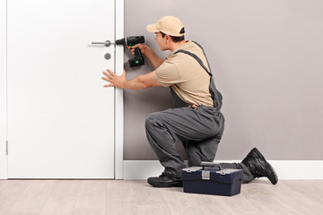 Young locksmith installing a lock on a door