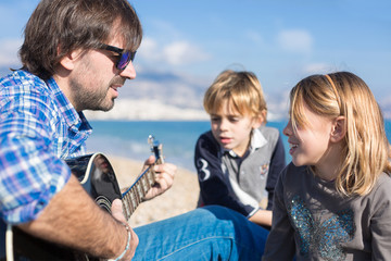Children and father singing song on beach