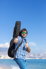 Portrait of bearded man with guitar showing thumbs up