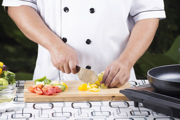 Chef cutting yellow bell pepper