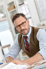 Businessman with eyeglasses sitting in front of desktop