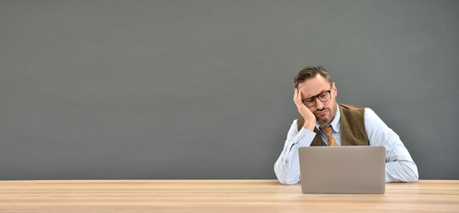 Middle aged man being bored in front of laptop, isolated