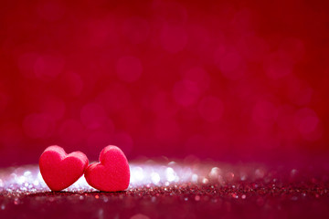 red Heart shapes on abstract light glitter background in love co