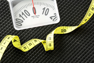 Measuring tape on black weight scale.