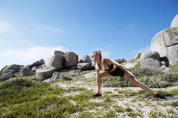 Young beautiful athlete stretching by rocks