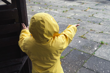 Little child in raincoat playing with water drops