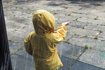 Little child in yellow raincoat plays with raindrops