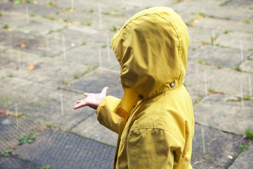 Little child in yellow raincoat playing with raindrops
